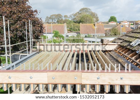Renovation projects. Building of extension of the existing house, unfinished wooden roof structure, steel beams,brick walls. steel beams, selective focus #1532052173