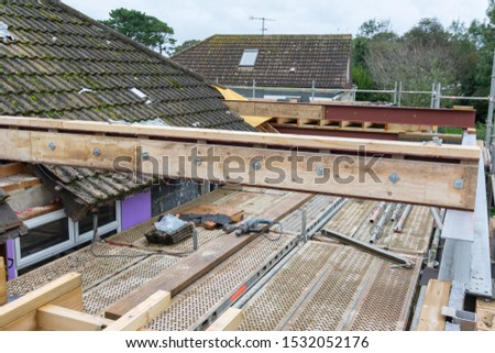 Renovation projects. Building of extension of the existing house, unfinished wooden roof structure, steel beams,brick walls. steel beams, selective focus #1532052176