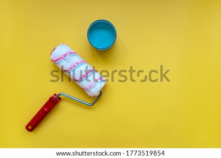 Renovation. Repair. New red paint roller for painting on yellow Background with blue acrylic paint. Top view, copy space. Space for text