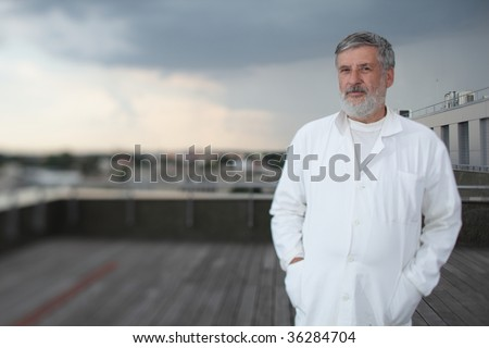 Renowned scientist/doctor standing on the roof of the research center/hospital looking confident