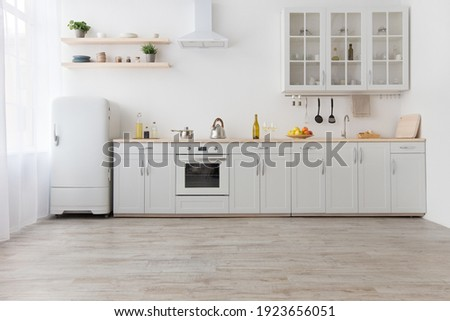 Rent of modern housing sale of new apartment, modern renovation. White furniture with utensils, shelves with crockery and plants in pots, refrigerator in simple minimal dining room, empty space