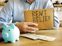 Rent relief. A man at home holds a handwritten lettering.