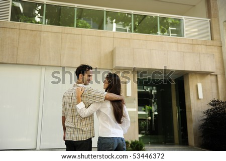 Renting or buying an apartment: Couple standing in front of their new flat