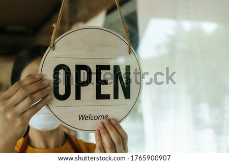"Reopen. waitress woman wearing protection face mask turning ""Open"" sign board reopen after coronavirus quarantine is over in cafe coffee shop ready to service, cafe restaurant, food and drink concept"