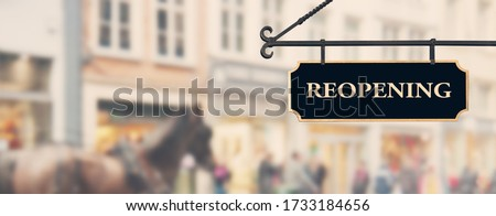 Reopening economy concept. Sign with word reopening hanging against open shop windows background. Restarting business after coronavirus lockdown. Economy recovery symbol