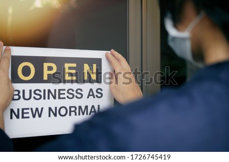 "Reopening for business adapt to new normal in the novel Coronavirus COVID-19 pandemic. Rear view of business owner wearing medical mask placing open sign ""OPEN BUSINESS AS NEW NORMAL"" on front door."