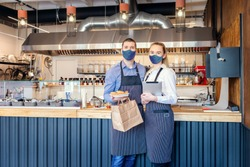 Reopening of a small business activity after the covid-19 lockdown quarantine with happy restaurant owners wearing face masks serving take away food orders and online deliveries