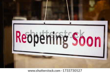 Reopening Soon Signage borad infront of Businesses or Restaurant door after covid-19 or coronavirus outbreak - Concept of back to business after pandemic.