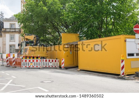 Repair and reconstruction of building, crane, yellow container and nature in the city. Reinforced concrete structures.