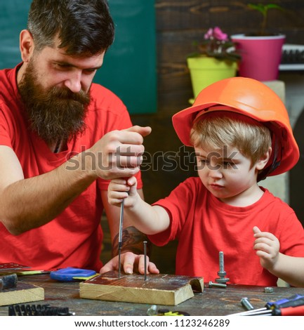 Repair and workshop concept. Father, parent with beard teaching little son to use tool screwdriver. Boy, child busy in protective helmet learning to use screwdriver with dad.