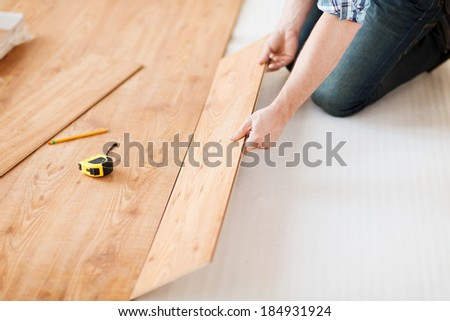 repair building and home concept close up of male hands intalling wood flooring