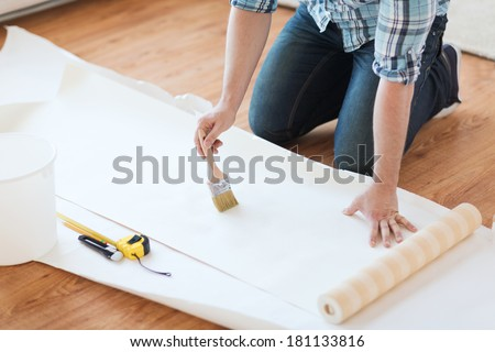 repair, building and home concept - close up of male hands smearing wallpaper with glue #181133816