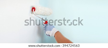 repair, building and home concept - close up of male in gloves painting wall with roller #394724563