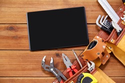 repair, building and renovation concept - tablet pc computer and belt with different work tools in pockets on wooden boards background