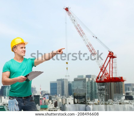 repair, building, construction and maintenance concept - smiling man in helmet with clipboard pointing finger
