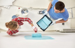 repair, building, people, teamwork and renovation concept - couple with paint and roller painting wall at home