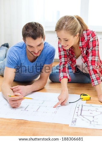 repair, building, renovation and home concept - smiling couple looking at blueprint at home #188306681
