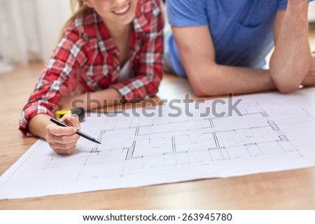 repair, building, renovation and people concept - close up of happy couple looking at blueprint at home #263945780