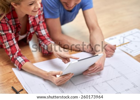 repair, building, renovation, architecture and technology concept - close up of couple with tablet pc and blueprint at home