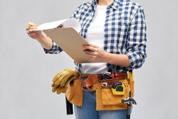 repair, construction and building concept - woman or builder with clipboard, pencil and working tools on belt over grey background