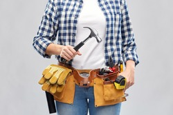 repair, construction and building concept - woman or builder with hammer and working tools on belt over grey background