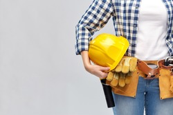 repair, construction and building concept - woman or builder with helmet and working tools on belt over grey background