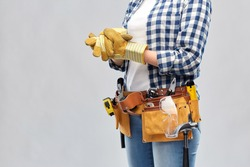 repair, construction and building concept - woman or builder with helmet and working tools on belt putting protective gloves on over grey background