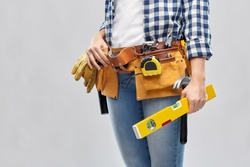 repair, construction and building concept - woman or builder with level and working tools on belt over grey background