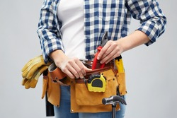 repair, construction and building concept - woman or builder with pliers and working tools on belt over grey background