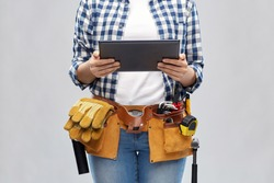 repair, construction and building concept - woman or builder with tablet pc computer working tools on belt over grey background