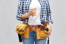 repair, construction and building concept - woman or builder with takeaway coffee cup and working tools on belt over grey background