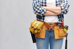 repair, construction and building concept - woman or builder with working tools on belt over grey background