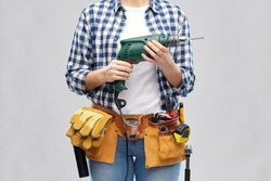 repair, construction and building concept - woman or builder with working tools on belt with electric drill or perforator over grey background