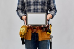 repair, construction and building - male worker or builder with working tools on belt showing tablet pc computer over grey background
