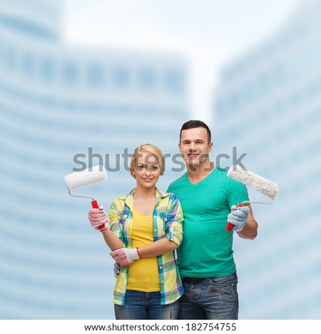 repair, construction and maintenance concept - smiling couple in gloves with paint rollers