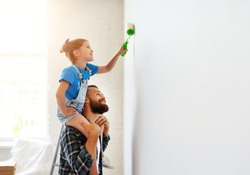 Repair in the apartment. Happy family father and child daughter  paints the wall with yellow paint