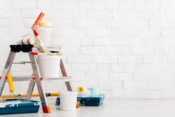 Repair, instruments and materials for painting walls, white bricks wall background, copy space