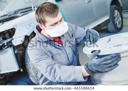 repair mechanic worker with light alloy car wheel disk rim Stock fotó ©