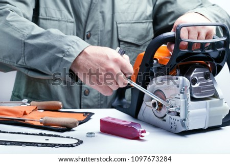Repair of chainsaws,gasoline powered tools. Man repairing chainsaw.
