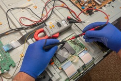 Repair of LCD TV in service center. Diagnostics of printed circuit board with multimeter probe. Selective focus.