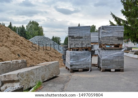 Repair of the road, sidewalk or square is made. On the street are piles of rubble, sand, old building concrete blocks and stacks of gray tiles or bricks covered with polyethylene
