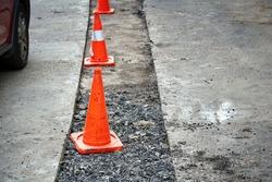 Repair pothole in asphalt pavement, road work warning cones. Roadwork, driveway repair, prepare for laying new asphalt. Damaged asphalt road surface repairing. Preparing for patch works