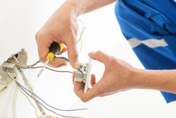 repair, renovation, electricity and people concept - close up of electrician hands with screwdriver fixing socket