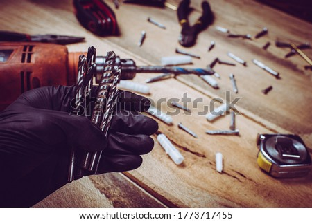 Repair technician hand holding set of metal drill bits with wall plugs in the background on wooden table.