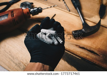 Repair technician hand holding wall plugs with tools in background.Wood works concept.