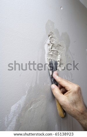 repair the damage to plaster a wall with gray paint