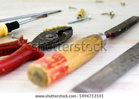 Repair tools on a wooden light background: file, pliers, pliers, screwdriver, screws, bolts