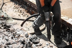 Repair work on the city street. Professional workers dismantle part of the road with a professional tool. Workers remove the asphalt and dig a hole. Technical experts, workflow on the city street
