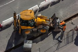 Repair work on the city streets using a heavy loader with a bucket for the construction of the road. Construction site for road works - top view. Public works, civil engineering, road construction.