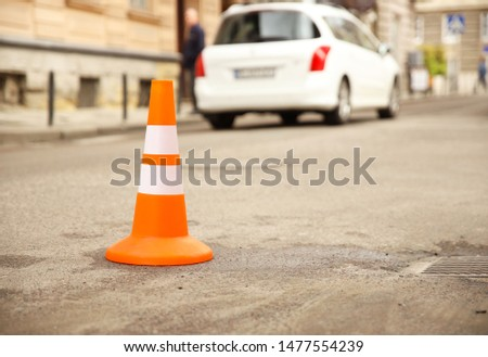 Repair work sign restricting traffic. White-orange plastic striped cone warning of danger. Tightening in traffic. Street of the old city with cars. Roadway repair. Poor asphalt on the road. Attention  #1477554239
